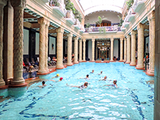 people in a swimming pool with ornate columns around them