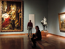 people viewing a large painting in a museum
