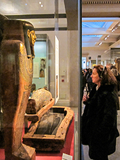 woman looking at a mummy in a museum in London's West End