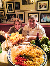 2 people sitting by a display of pasta in London's West End