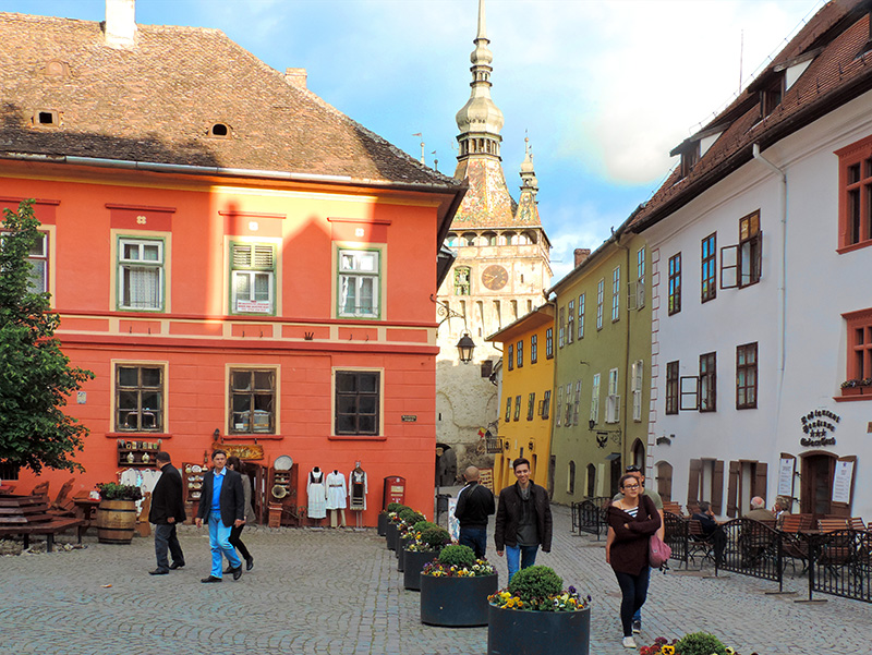 travelers walking about Sighisoara, one of the best things to do in Romania