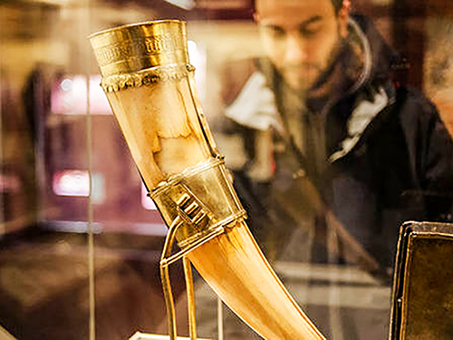 a gold encrusted hunting horn in a museum case