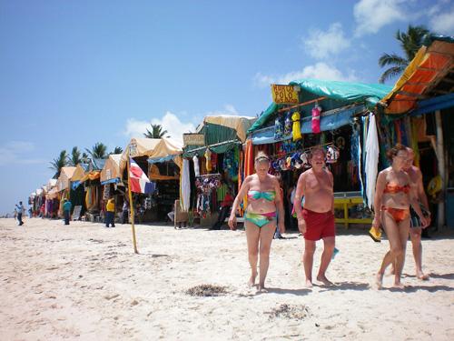 people walking past shacks on a beach