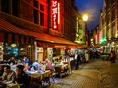 people eating at outdoor cafes at night