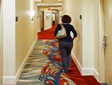 a woman walking down a hotel hallway