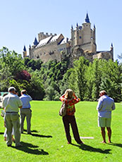 people looking up at a castle in Segovia