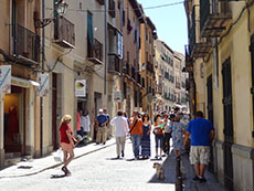 people on a street lined with old buildings in Segovia
