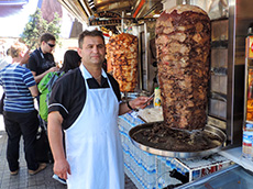man standing by a large rotisserie
