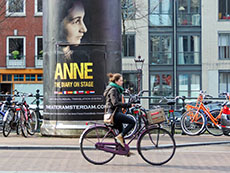 a young woman on a bicycle passing an advertising poster in Amsterdam