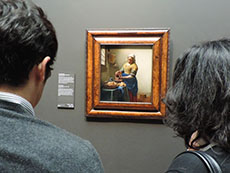 2 people looking at a mslal painting