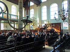 Men sitting in pews in a synagopgue in Amsterdam