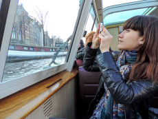 young woman taking a photo from a boat in Amsterdam