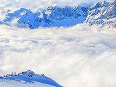buildings and mountains above the clouds