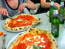 sampling pizza on a plate in Naples - one of the enjoyable European experiences