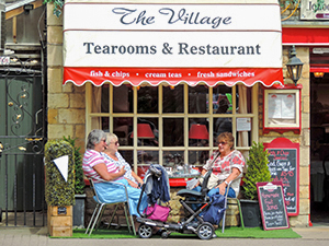 women having tea in front of an old shop, one of the best things to do in the Cotswolds