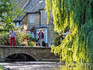 people on a small stone bridge in England, one of the best things to do in the Cotswolds