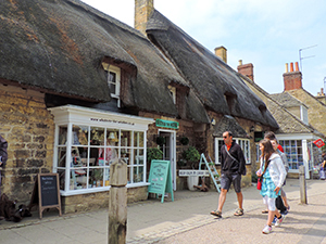 people walking by thatched-roof buildings in England