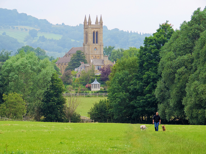 a view of an old church across a field, one of the best things to do in the Cotswolds