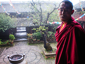a Chinese monk standing in a doorway in in Lijiang
