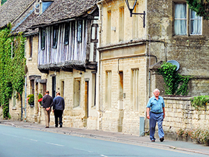 people walking by old timbered houses in England