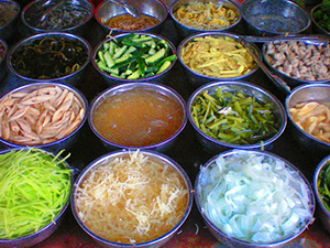 bowls in a market with brighly colored food in Lijiang