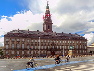 bicyclists riding past an old building with a spire in Copenhagen