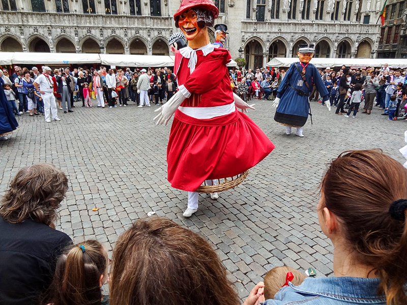 large paper mache characters seen dancing in a square on a weekend in Brussels