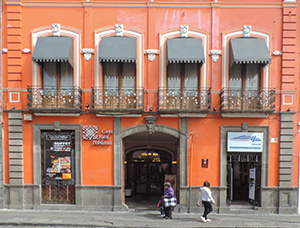 an orange-colored building with wrought-iron balconies, one of the things to see in Puebla