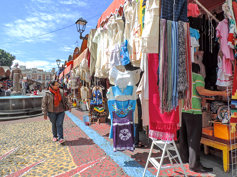 woman walking through an outdoor market, one of the fun things to do in Puebla
