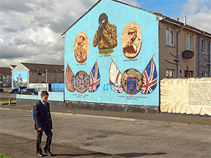 boy walking past a wall mural seen on a Black Taxi tour of Belfast
