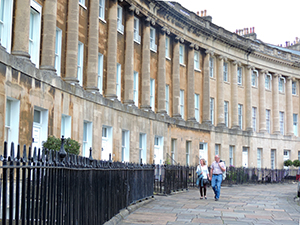 a couple walking by teh Royal Crescent, a popular place to visit on a day trip from London