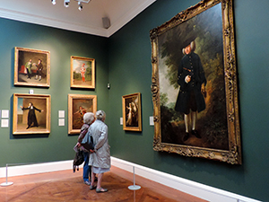 people looking at a painting in a museum
