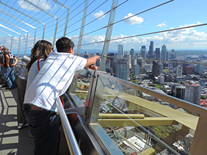 people looking at a city skyline from atop the Space Needle