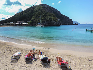 People lieing on the beach at Palaiokastrítsa, one of the popular things to do in Corfu