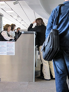 a woman at a airline ticket counter - passengers should know how to be compensated for a delayed flight