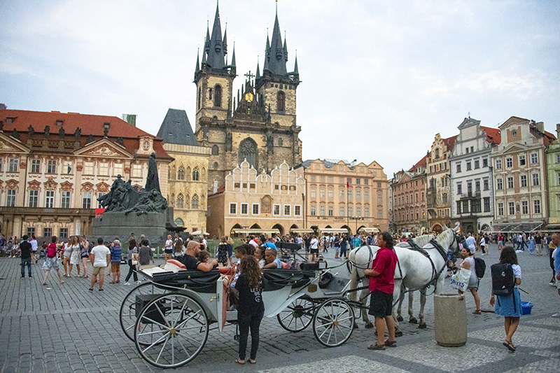 people and a hrose-drawn carriage on an old city square