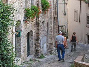 people walking down a small street in an Italian hill town