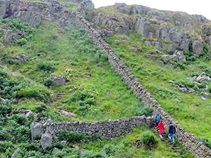 people walking along an old wall