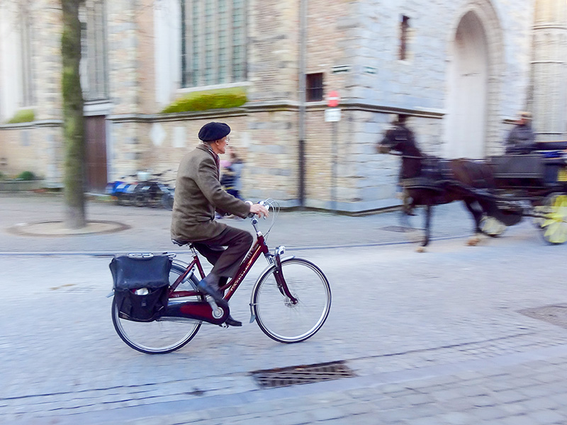 man on a bicycle Bruges, Belgium, during the best time to visit Bruges