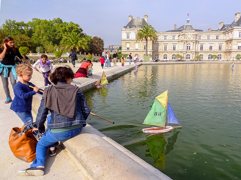 boy sailing a boat on a pond in Luxembourg Gardens