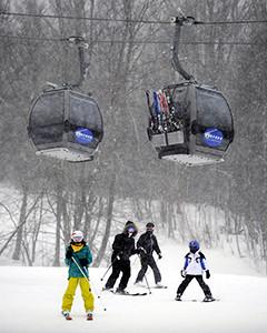 skiers under ski gondolas
