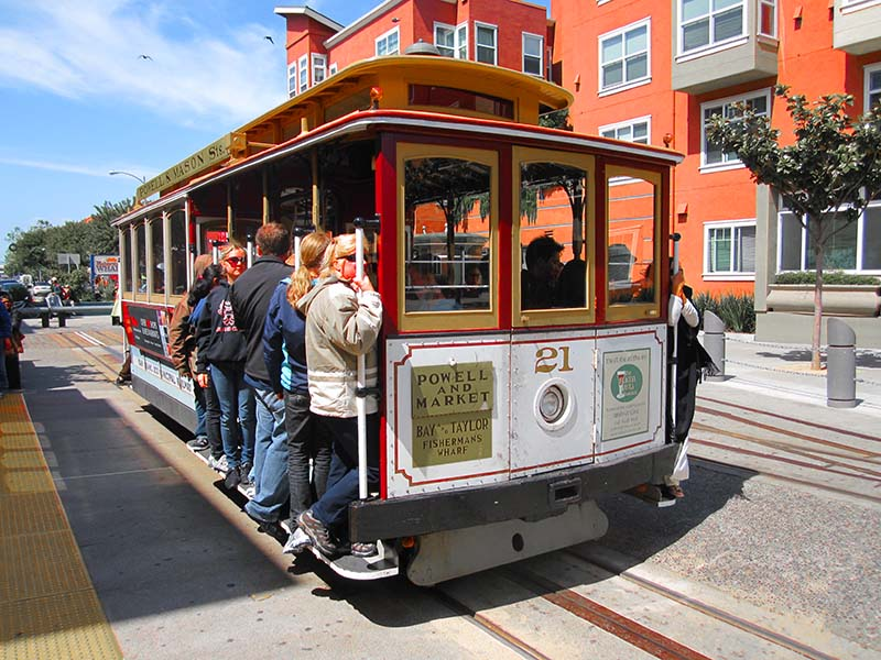 people riding a cable car, one of the things to do during 3 days in San Francisco