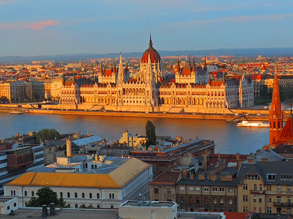 a large building on a river in Budapest