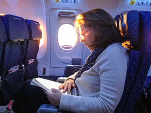 woman reading book on a plane air-travel