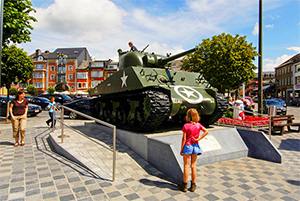 a girl looking at an army tank
