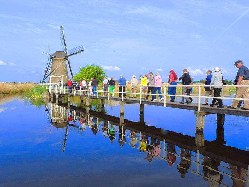 people walking on a bridge to a windmill on a Viking Rhine River cruise