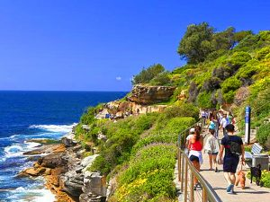 people walking along teh ocean in Sydney