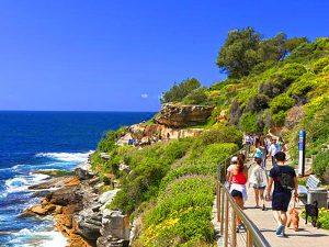 people walking along teh ocean in Sydney
