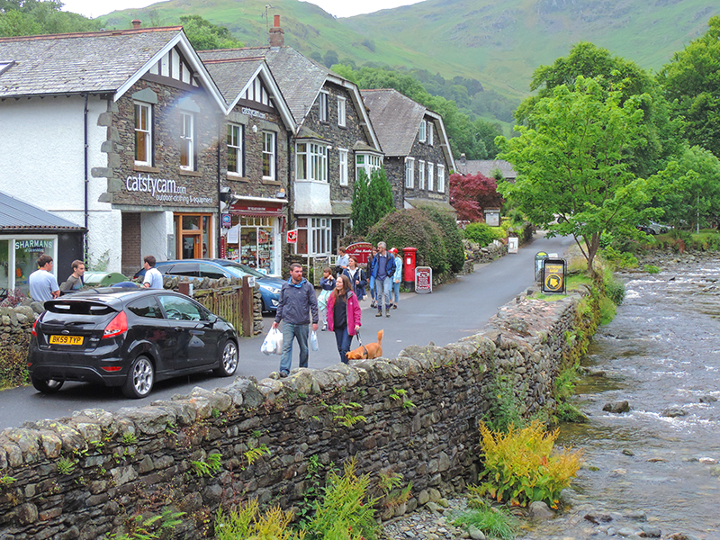 people walking through a country town in England