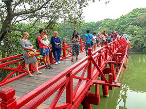 people on a red-painted bridge